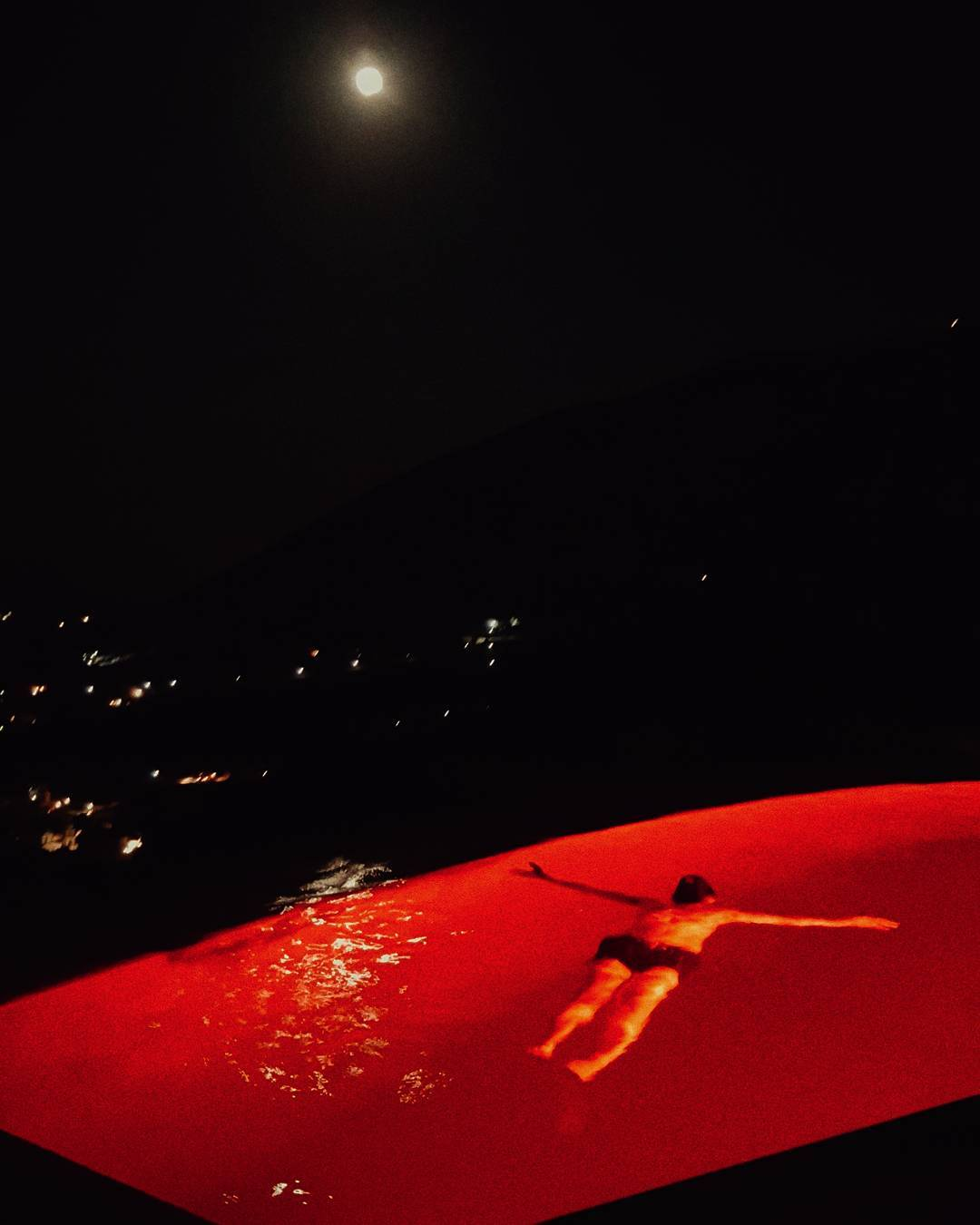 Almost a full moon tonight and we've set the pool lights to funky splatter red. Photo by my better half.